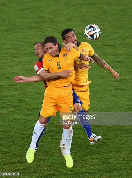 Marcelo Diaz of Chile goes up for a header against Mark Milligan and Tim Cahill of Australia during the 2014 FIFA World Cup Brazil Group B match...
