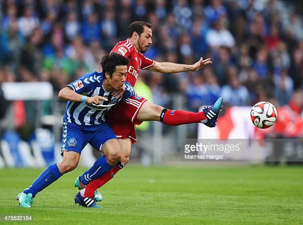 Marcelo Diaz of Hamburger SV holds off Hiroki Yamada of Karlsruher SC during the Bundesliga playoff second leg match between Karlsruher SC and...