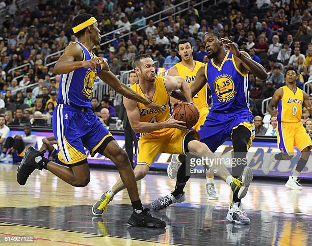 Marcelo Huertas of the Los Angeles Lakers drives to the basket between Patrick McCaw and Klay Thompson of the Golden State Warriors during their...