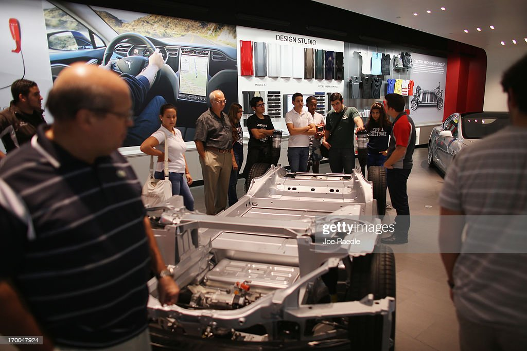 Marcelo Jaramillo, assistant store manager, (R) explains how the Tesla motor company car works in a dealership at the Dadeland Mall on June 6, 2013 in Miami, Florida. The electric car maker is trying to make a move by selling their cars, that can cost between $62,400 and $82,400, into malls and stores.