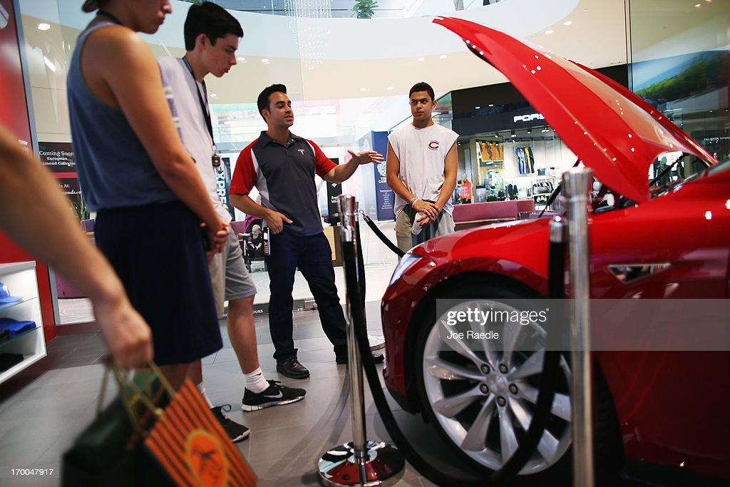 Marcelo Jaramillo, assistant store manager, (2nd R) shows a Tesla motor company car in a dealership at the Dadeland Mall on June 6, 2013 in Miami, Florida. The electric car maker is trying to make a move by selling their cars, that can cost between $62,400 and $82,400, into malls and stores.