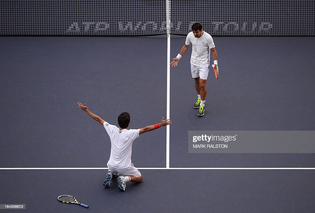 Marcelo Melo of Brazil (L) and Ivan Dodig of Croatia (R) celebrate after defeating David Marrero and Fernando Verdasco of Spain during their men's doubles finals at the Shanghai Masters 1000 tennis tournament held in the Qizhong Tennis Stadium in Shanghai on October 13, 2013. Dodig and Melo went on to win 7-6, 6-7, 1(10)-0 (2). AFP PHOTO /Mark RALSTON