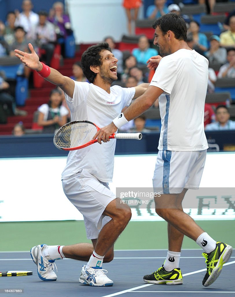 Marcelo Melo of Brazil (L) and Ivan Dodig of Croatia (R) celebrate after defeating David Marrero and Fernando Verdasco of Spain during their men's doubles finals at the Shanghai Masters 1000 tennis tournament held in the Qizhong Tennis Stadium in Shanghai on October 13, 2013. Dodig and Melo won 7-6, 6-7, 1(10)-0 (2). AFP PHOTO/Peter PARKS