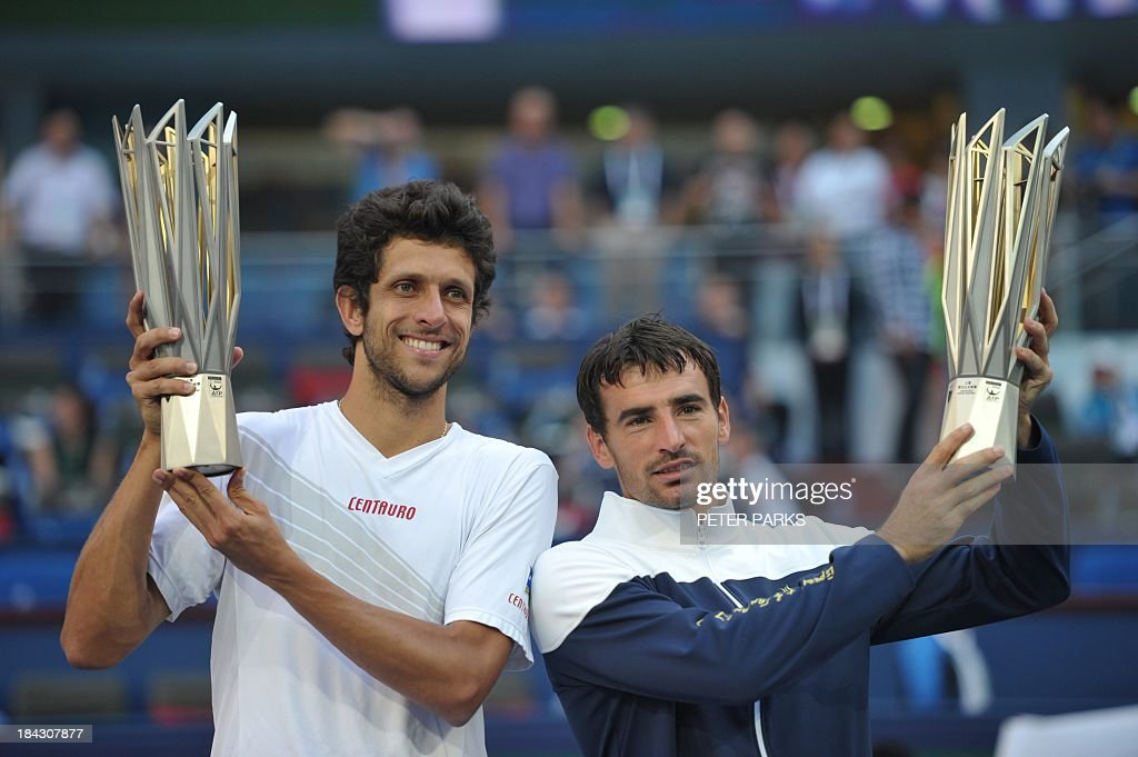 Marcelo Melo of Brazil (L) and Ivan Dodig of Croatia (R) hold their trophies after defeating David Marrero and Fernando Verdasco of Spain during their men's doubles finals at the Shanghai Masters 1000 tennis tournament held in the Qizhong Tennis Stadium in Shanghai on October 13, 2013. Dodig and Melo won 7-6, 6-7, 1(10)-0 (2). AFP PHOTO/Peter PARKS
