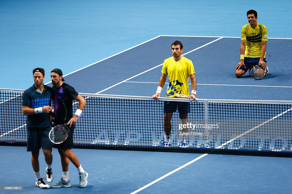 Marcelo Melo of Brazil and Ivan Dodig of Croatia (on knees) look to the screen after Lukasz Kubot of Poland and Robert Lindstedt of Sweden challenged a point in the doubles semi-final match on day seven of the Barclays ATP World Tour Finals at O2 Arena on November 15, 2014 in London, England.