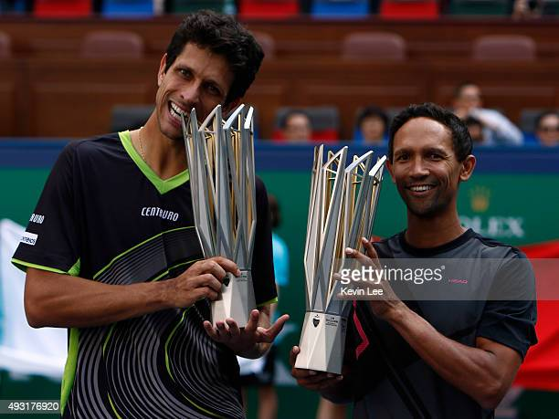 Marcelo Melo of Brazil and Raven Klaasen of Republic of South Africa hold their trophy at the award ceremony after winning the match against Simone...