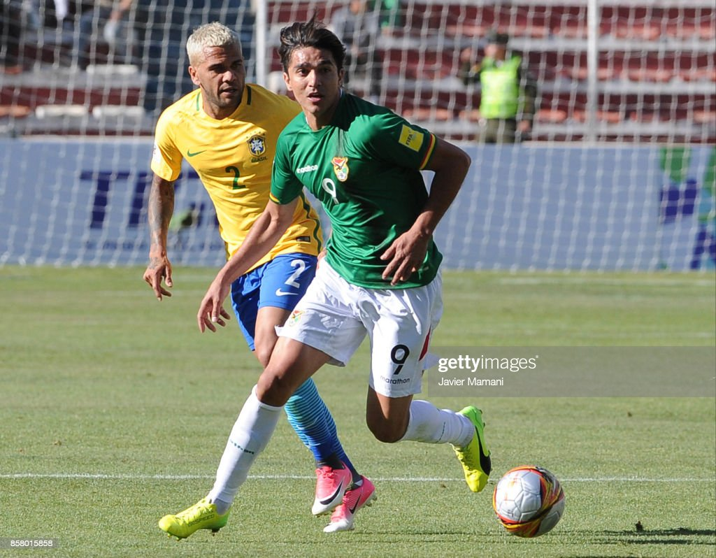 Marcelo Moreno Martins of Bolivia drives the ball followed by Dani Alves of Brazil during a match between Bolivia and Brazil as part of FIFA 2018 World Cup Qualifiers at Hernando Siles Stadium on October 05, 2017 in La Paz, Bolivia.