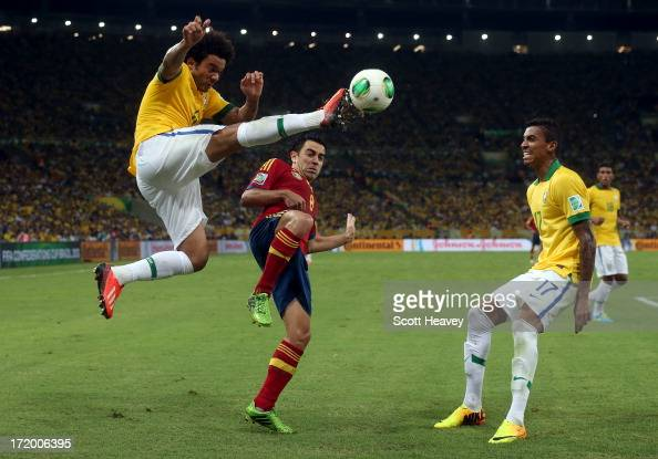 Marcelo of Brazil beats Xavi Hernandez of Spain to the ball during the FIFA Confederations Cup Brazil 2013 Final match between Brazil and Spain at...