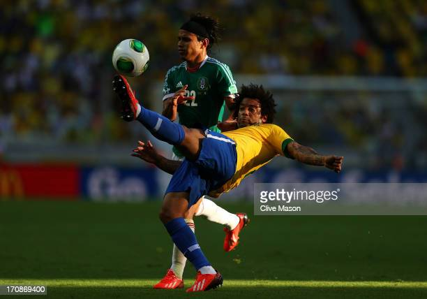 Marcelo of Brazil competes with Gerardo Flores of Mexico during the FIFA Confederations Cup Brazil 2013 Group A match between Brazil and Mexico at...