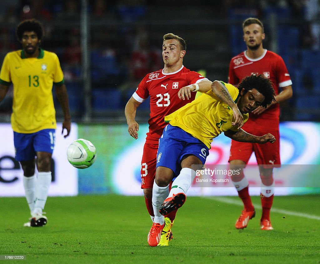 Marcelo of Brazil (R) is challenged by <a gi-track='captionPersonalityLinkClicked' href=/galleries/search?phrase=Xherdan+Shaqiri&family=editorial&specificpeople=6923918 ng-click='$event.stopPropagation()'>Xherdan Shaqiri</a> of Switzerland during the international friendly match between Switzerland and Brazil at St. Jakob Stadium on August 14, 2013 in Basel, Switzerland.