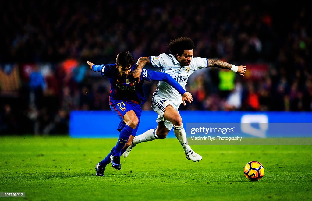 Marcelo of Real Madrid battles for the ball with Andre Gomes of Barcelona during the La Liga match between FC Barcelona and Real Madrid CF at Camp...