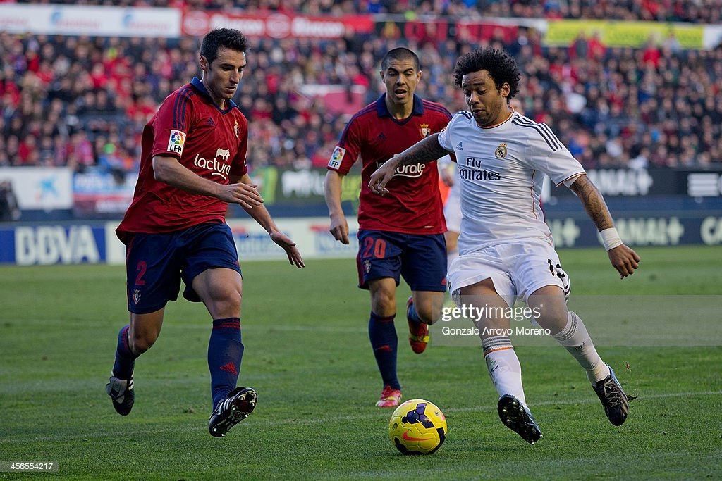 Marcelo (R) of Real Madrid CF competes for the ball with Marc Bertran (L) of CA Osasuna and his teammate Francisco Andres Silva (2ndR) during the La Liga match between CA Osasuna and Real Madrid CF at Estadio El Sadar de Navarra on December 14, 2013 in Pamplona, Spain.