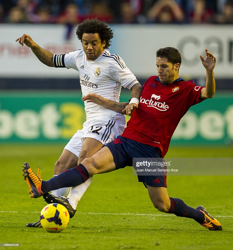 Marcelo of Real Madrid CF duels for the ball with Alvaro Cejudo of CA Osasuna during the La Liga match between CA Osasuna and Real Madrid CF at Estadio Reyno de Navarra on December 14, 2013 in Pamplona, Spain.