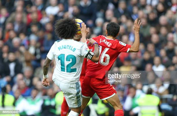 Marcelo of Real Madrid CF is challenged by Sevilla's Spanish midfielder Jesus Navas during the La Liga match between Real Madrid and Sevilla at...