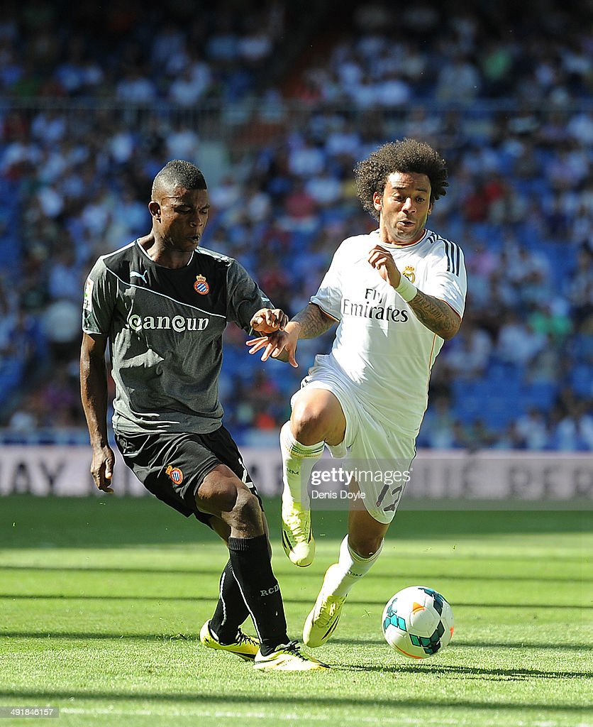 Marcelo of Real Madrid CF is tackled by John Cordoba of RCD Espanyol during the La Liga match between Real Madrid CF and RCD Espanyol at Santiago Bernabeu stadium on May 17, 2014 in Madrid, Spain.