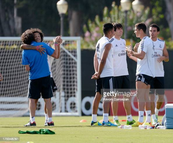 Marcelo of Real Madrid clowns with a trainer as teammates Cristiano Ronaldo Pepe Kaka and Carlos Henrique Casimiro talk during a training session at...