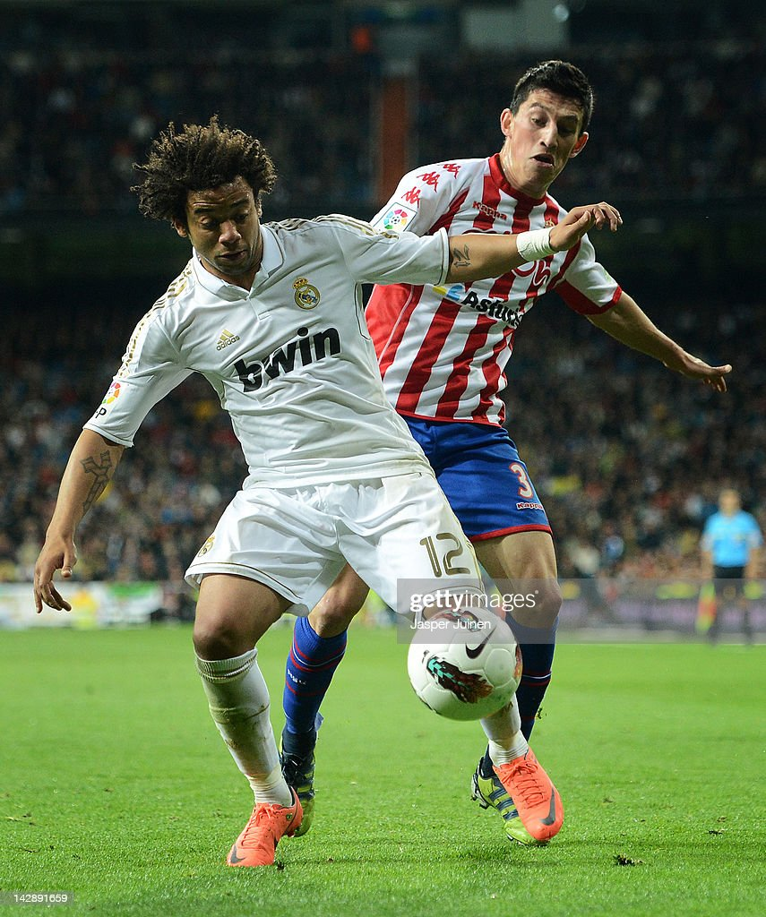 Marcelo (L) of Real Madrid duels for the ball with <a gi-track='captionPersonalityLinkClicked' href=/galleries/search?phrase=Andre+Castro&family=editorial&specificpeople=7124527 ng-click='$event.stopPropagation()'>Andre Castro</a> of Real Sporting de Gijon during the La Liga match between Real Madrid CF and Real Sporting de Gijon at the Estadio Santiago Bernabeu on April 14, 2012 in Madrid, Spain.