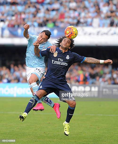 Marcelo of Real Madrid heads the ball beside Fabian Orellana of Celta Vigo during the La Liga match between Celta Vigo and Real Madrid at Estadio...