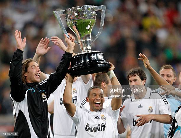 Marcelo of Real Madrid holds aloft the La Liga trophy flanked by his teammates Sergio Ramos and Ruud van Nistelrooy at the end of the La Liga match...