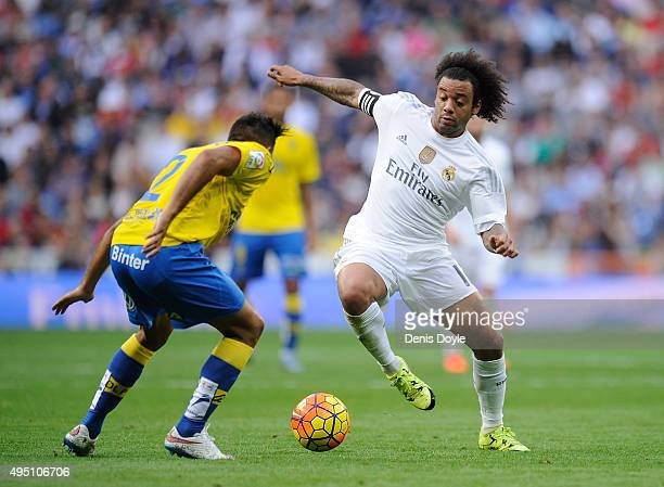 Marcelo of Real Madrid is tackled by David Simon of UD Las Palmas during the La Liga match between Real Madrid CF and UD Las Palmas at Estadio...
