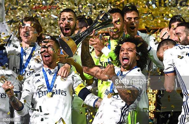 Marcelo of Real Madrid lifts the trophy as him and his team mates celebrate victory following the FIFA Club World Cup Final match between Real Madrid...