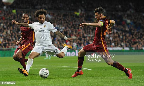 Marcelo of Real Madrid shoots past Alessandro Florenzi and Seydou Keita of AS Roma during the UEFA Champions League Round of 16 Second Leg match...