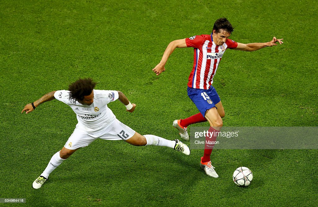 <a gi-track='captionPersonalityLinkClicked' href=/galleries/search?phrase=Marcelo+-+Attacking+Left+Back+-+Born+1988&family=editorial&specificpeople=2136789 ng-click='$event.stopPropagation()'>Marcelo</a> of Real Madrid tackles <a gi-track='captionPersonalityLinkClicked' href=/galleries/search?phrase=Stefan+Savic&family=editorial&specificpeople=6135329 ng-click='$event.stopPropagation()'>Stefan Savic</a> of Atletico Madrid during the UEFA Champions League Final match between Real Madrid and Club Atletico de Madrid at Stadio Giuseppe Meazza on May 28, 2016 in Milan, Italy.