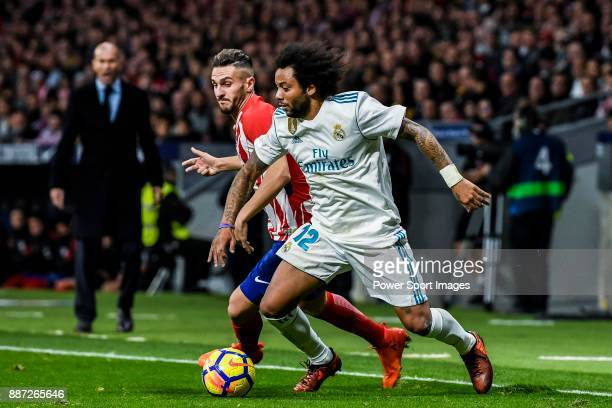Marcelo Vieira Da Silva of Real Madrid battles for the ball with Saul Niguez Esclapez of Atletico de Madrid during the La Liga 201718 match between...