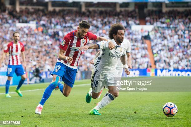 Marcelo Vieira Da Silva of Real Madrid competes for the ball with Yannick Ferreira Carrasco of Atletico de Madrid during their La Liga match between...