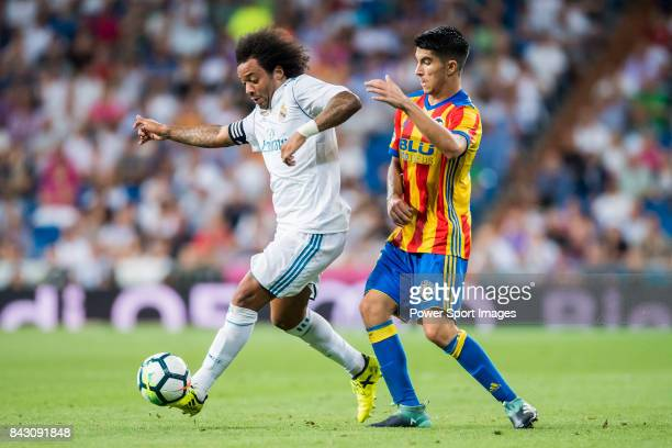 Marcelo Vieira Da Silva of Real Madrid fights for the ball with Carlos Soler Barragan of Valencia CF during their La Liga 201718 match between Real...
