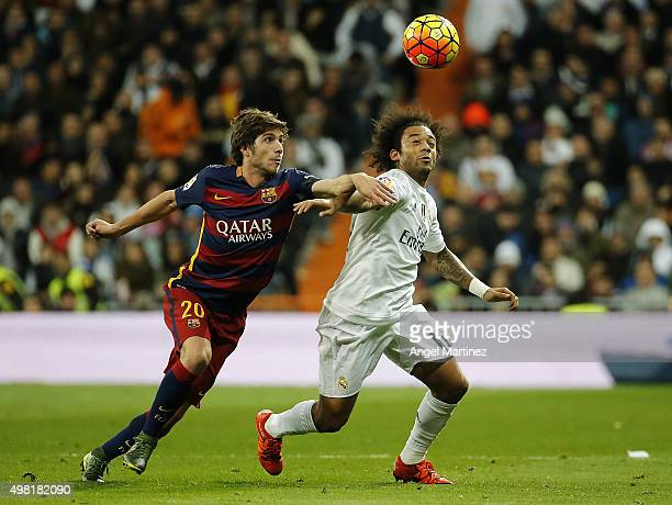 Marcelo Vieira of Real Madrid competes for the ball with Sergi Roberto of FC Barcelona during the La Liga match between Real Madrid CF and FC...