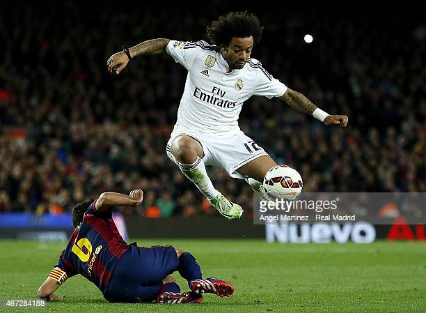 Marcelo Vieira of Real Madrid jumps over Xavi Hernandez of FC Barcelona during the La Liga match between FC Barcelona and Real Madrid CF at Camp Nou...