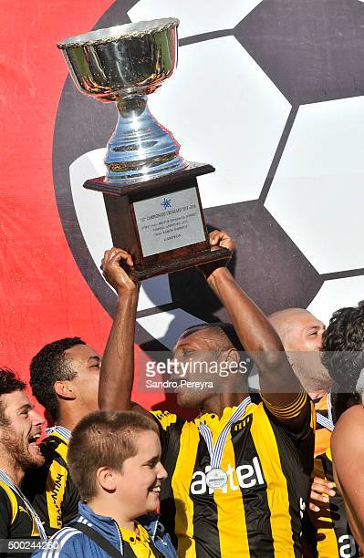 Marcelo Zalayeta of Peñarol raises the trophy after a match between Penarol and Juventud as part of Torneo Apertura 2015 at Centenario Stadium on...