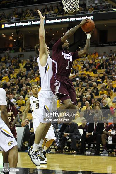 Mississippi State Bulldogs guard Fred Thomas puts the ball up past Missouri Tigers forward Ryan Rosburg during the NCAA men's basketball game between...