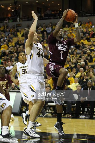 Mississippi State Bulldogs guard Fred Thomas puts the ball up in front of Missouri Tigers forward Ryan Rosburg during the NCAA men's basketball game...