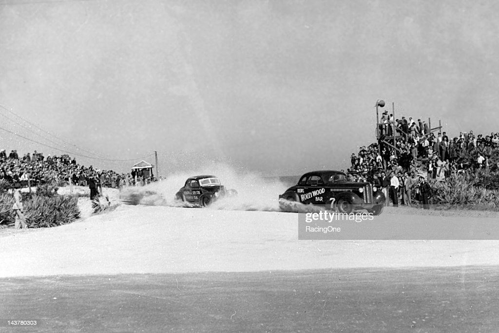 Joe Littlejohn in a 1939 Buick leads Roy Hall's 1939 Ford off the north turn of the Daytona BeachRoad Course during the 160mile stock car race...