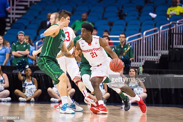 Damyean Dotson of Houston dribbles by Rick Smith of Tulane during the AAC Championship Tournament between Tulane and Houston at the Amway Center in...