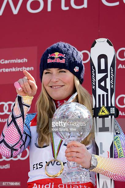 Lindsey Vonn with the crystal globe for the overall Super G title points at her parents in law during the medal award ceremony at the Audi FIS Alpine...