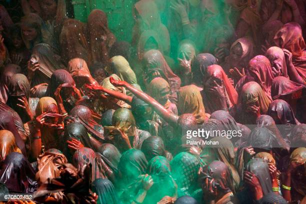 Indian women cover their faces with their sari as coloured power is powered over them as tens of thousands of Indian celebrate Holi the festival of...
