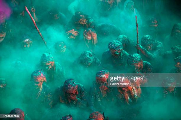Men cover their faces as coloured power is poured over them as tens of thousands of Indian celebrate Holi the festival of colours at a temple on...