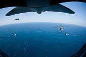 March 18, 2011 - An MC-130P Combat Shadow crew prepares to refuel two HH-60G Pave Hawk helicopters above the Pacific Ocean.
