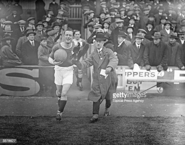 A Manchester City fan offers his team's captain a mascot as he takes to the pitch to play Newcastle United
