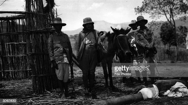 Photojournalists pose with their Abyssinian escort and their donkey