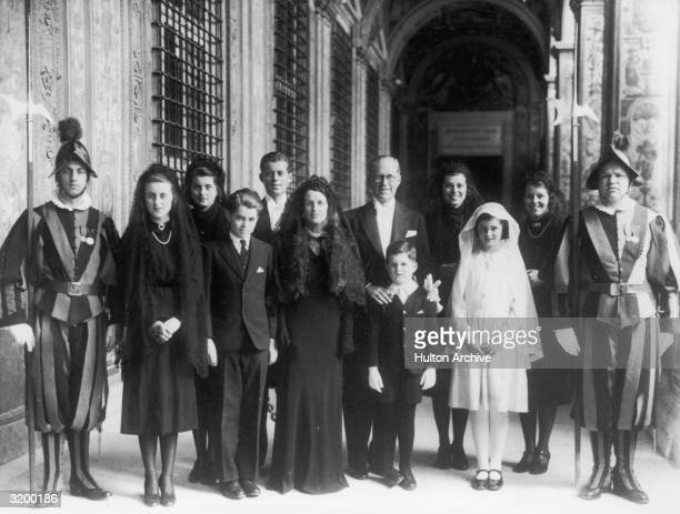 US ambassador to England Joseph P Kennedy his wife Rose and eight of their children standing between two guards outside the Papal residence at their...