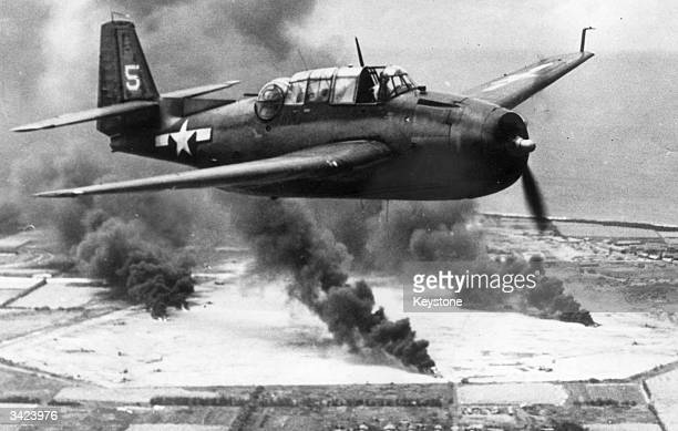 A US Navy Avenger torpedo bomber soars above the Japaneseheld Tinian Island part of the Commonwealth of Mariana Island where installations are...