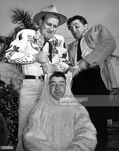 A portrait of Bud Abbott and actor Robert Mitchum pulling on either ear of Lou Costello's rabbit costume during an Easter party at Costello's home