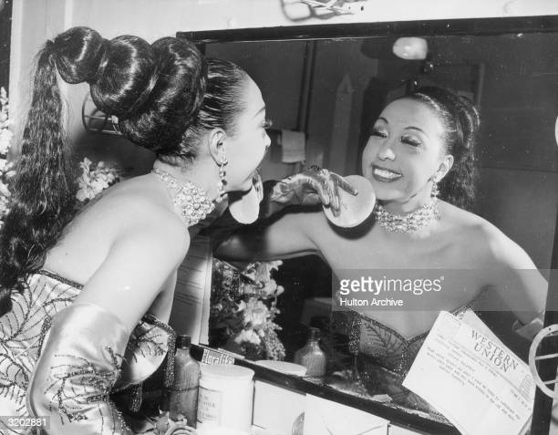 Americanborn cabaret singer Josephine Baker applies makeup with a powder puff in her dressing room before a performance at the Strand Theatre A...