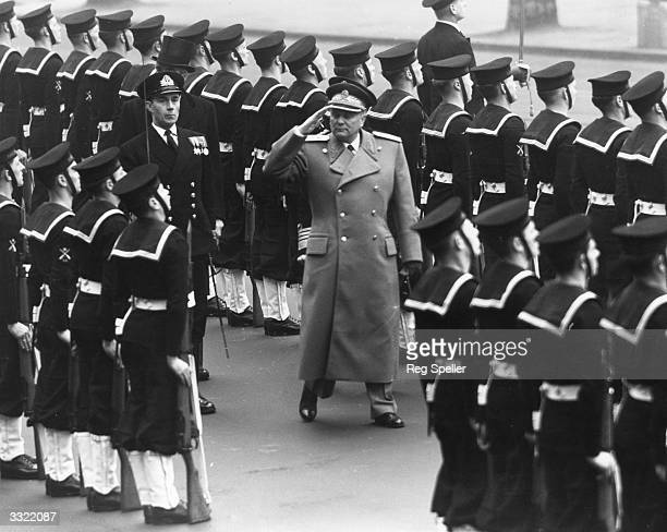 Marshal Tito the Yugoslav guerrilla and ruler of Yugoslavia taking a salute at a military parade before leaving Britain