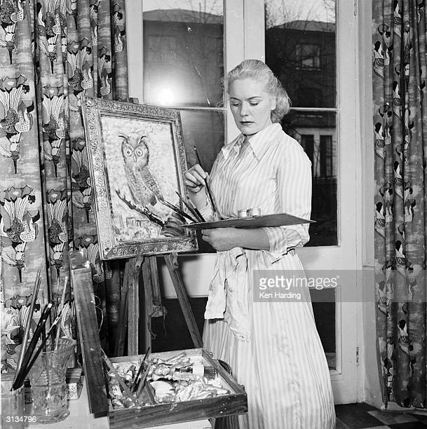 Glamorous strongwoman Joan Rhodes paints for relaxation in her flat in Hampstead north London
