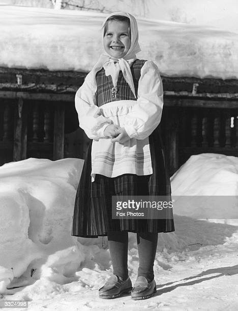 A young Norwegian girl wearing national costume in the snow at Lillehammer in Norway